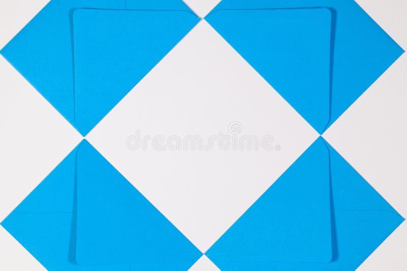De blauwe enveloppen op de witte lijst stock foto