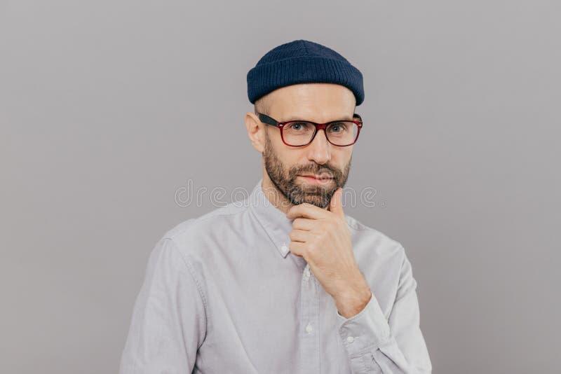 De blauwe eyed mannelijke volwassene houdt kin en bekijkt aandachtig camera, nadenkt op uitweg of de oplossing, draagt bril, hoof stock foto