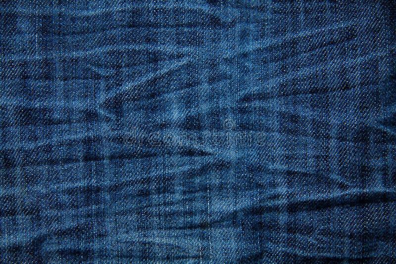 De blauwe gerimpelde textuur van denimjeans, achtergrond stock afbeelding