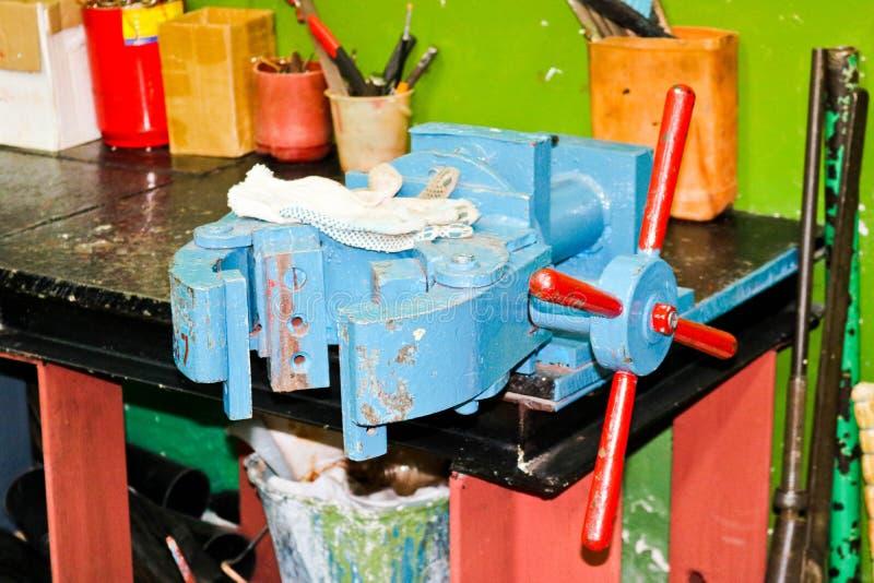 De blauwe grote industriële ondeugd van het ijzermetaal en werkende handschoenen in de workshop bij de fabriek stock foto's