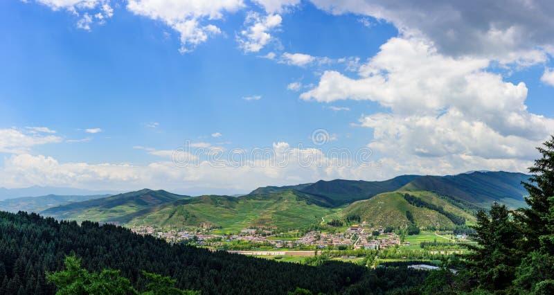 De blauwe hemel, de witte wolken, de groene bergen en de grasring rond het mooie dorp royalty-vrije stock fotografie