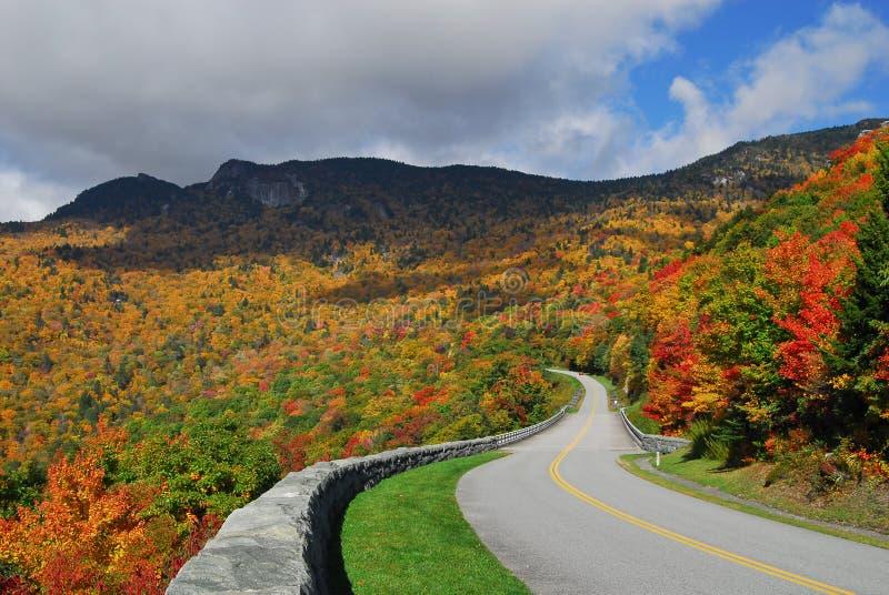 De blauwe Herfst van het Brede rijweg met mooi aangelegd landschap van de Rand Toneel stock afbeeldingen