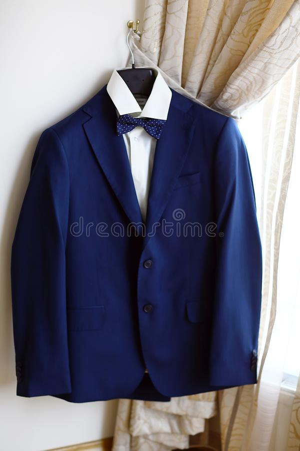 De blauwe kostuum en bandvlinder, wit overhemd, dat op de muur hangt, kleedt zich voor de bruidegom in de ruimte, een reeks van k stock foto's