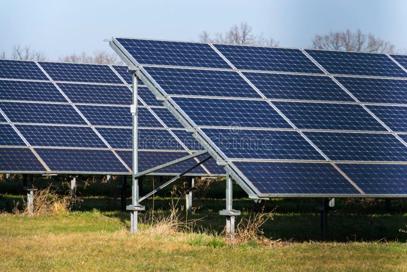 De blauwe krachtcentrale van zonnepanelenphotovoltaics met bomen op achtergrond royalty-vrije stock foto's