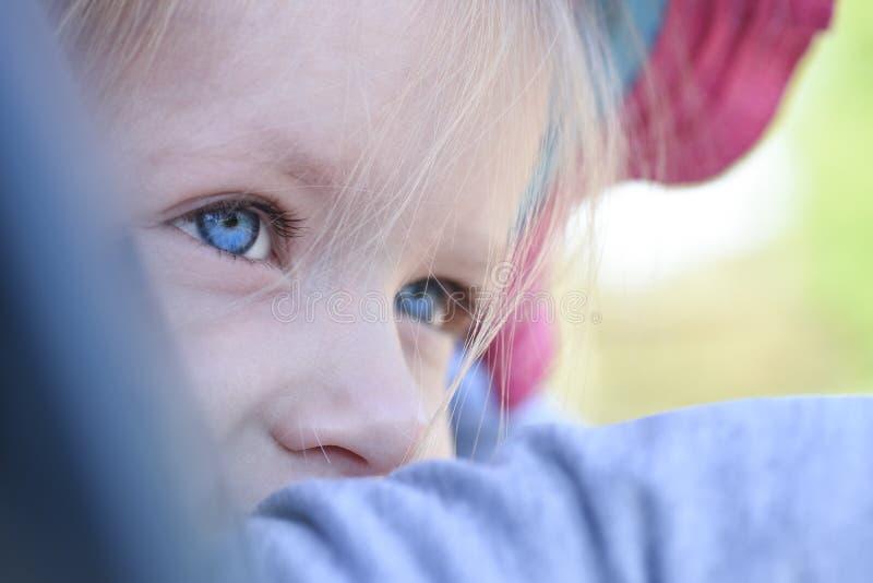 De blauwe ogenmeisjes kijken omhoog, close-up, autodeur stock afbeeldingen