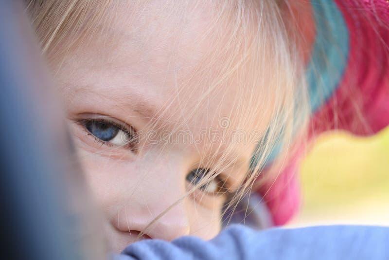 De blauwe ogenmeisjes zijn droevig, close-up, autodeur stock foto