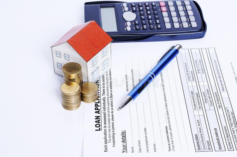 De blauwe pen met muntstukken stapelt en huisvest document en calculator op leningentoepassing stock foto
