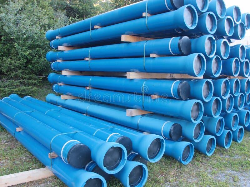 De blauwe pijpen en de montage van pvc plastic die voor ondergrondse watervoorziening en rioollijnen worden gebruikt stock foto's