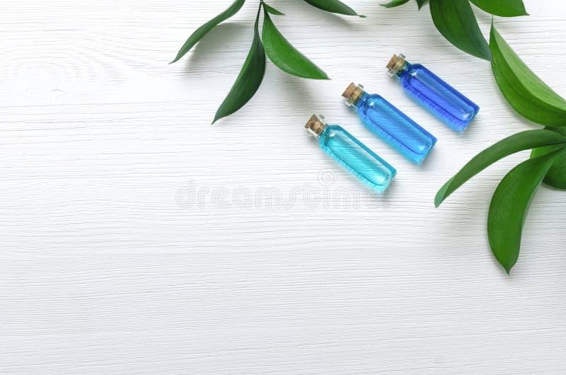 De blauwe tint van de essentieolie op witte houten achtergrond stock afbeeldingen
