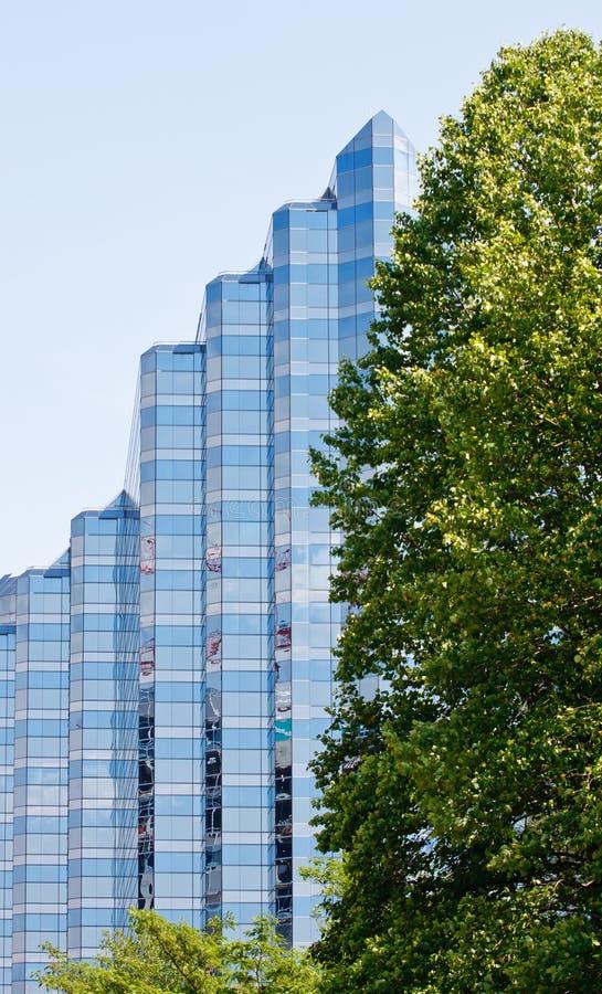 De blauwe Toren van het Glas voorbij Groene Bomen stock foto