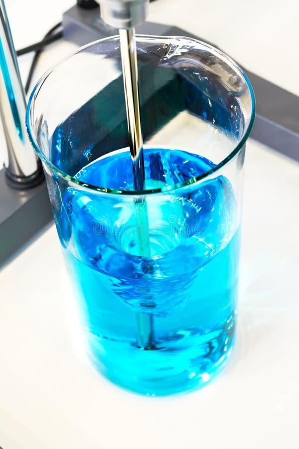 De blauwe vloeistof is gemengde laboratoriumopruier royalty-vrije stock fotografie