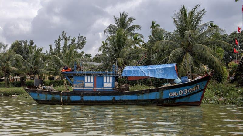 De blauwe werkende vissersboot verankerde langs de bank van Thu Bon River in Hoi An, Vietnam royalty-vrije stock foto