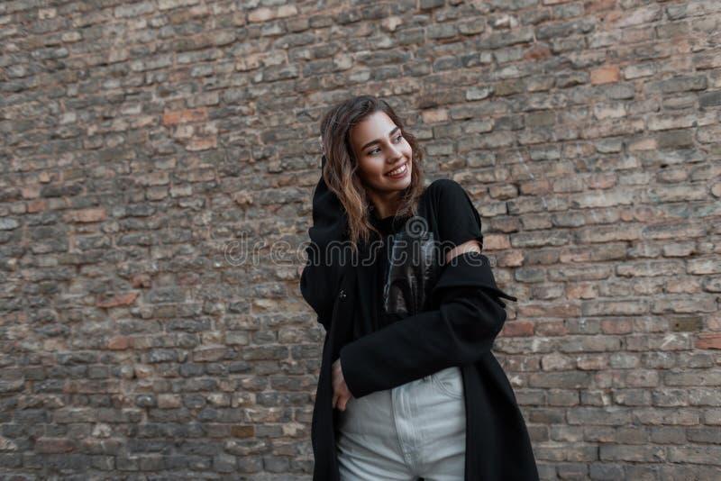De blije aantrekkelijke jonge vrouw met een leuke glimlach in een modieuze laag in een zwarte T-shirt in modieuze witte jeans ste stock foto
