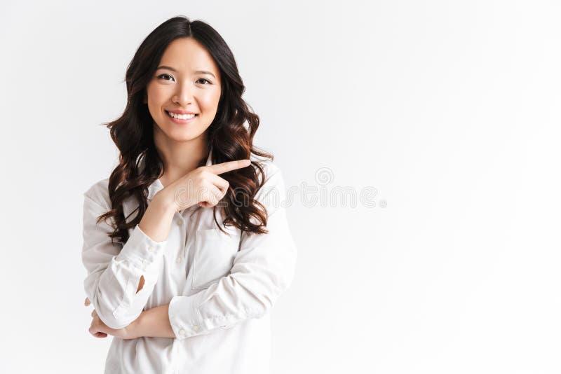 De blije Aziatische vrouw die met lang donker haar camera bekijken met is stock fotografie