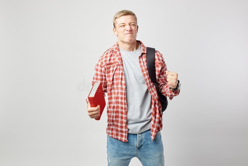De blije blonde kerel met zwarte rugzak op zijn schouder gekleed in een witte t-shirt, een rode geruite overhemd en jeans houdt royalty-vrije stock foto's