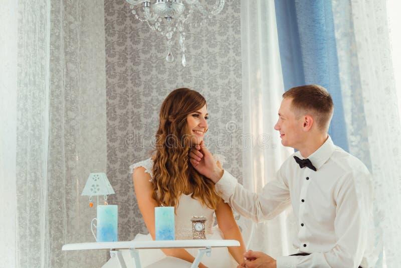 De blije bruidegom houdt bride& x27; s kin terwijl zij zitten stock foto's