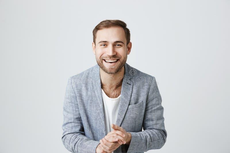 De blije blije Europese gebaarde vrolijke mens die met resultaten van het werk, glimlachen ruim bij camera worden tevredengesteld stock fotografie