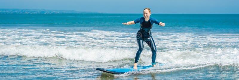 De blije jonge surfer van de vrouwenbeginner met blauwe branding heeft pret op kleine overzeese golven Actieve familielevensstijl royalty-vrije stock foto's