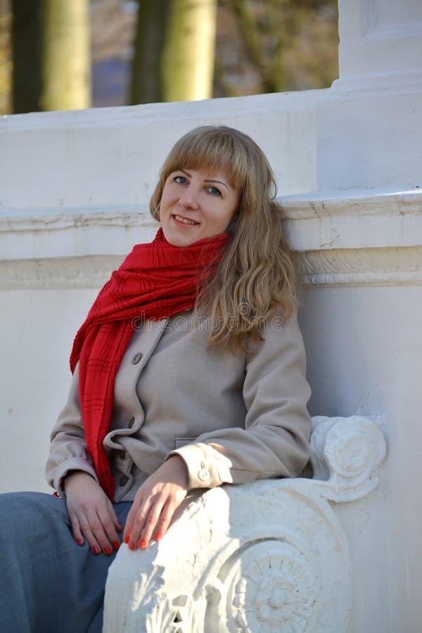 De blije jonge vrouw heeft een rust op een bank in het park royalty-vrije stock foto's