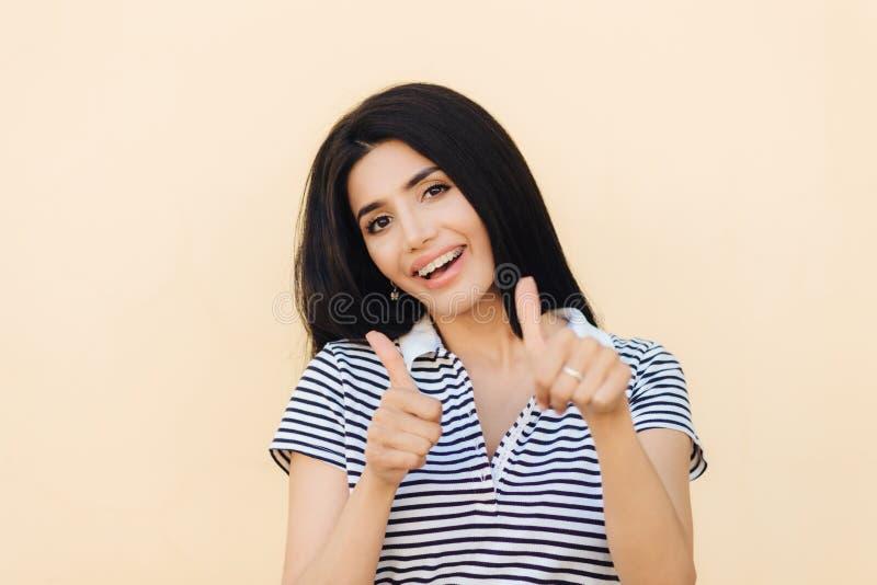 De blije jonge vrouwelijke dame houdt duimen opgeheven omhoog, goedkeurt iets met optimistische uitdrukking, gekleed in toevallig stock foto