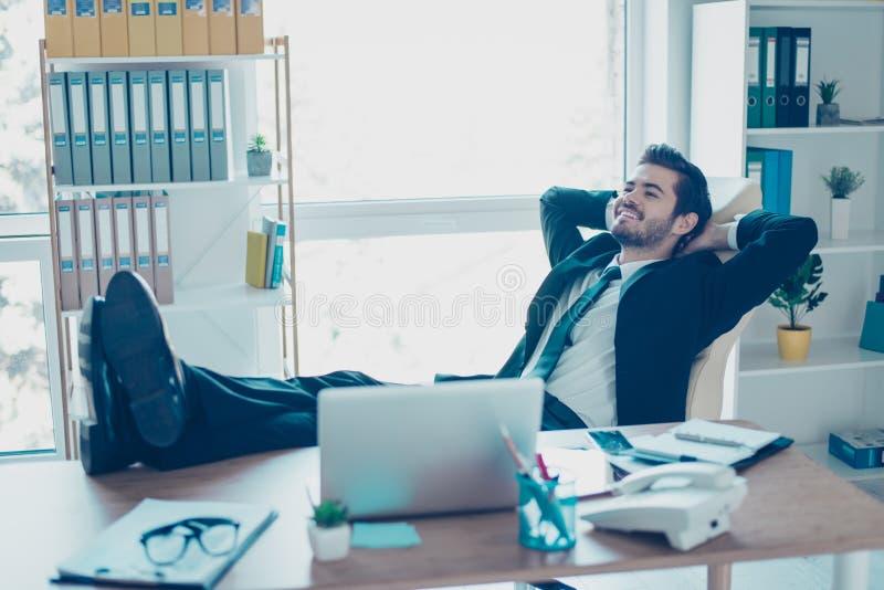 De blije jonge zakenman rust omhoog in zijn bureau met voeten stock foto's