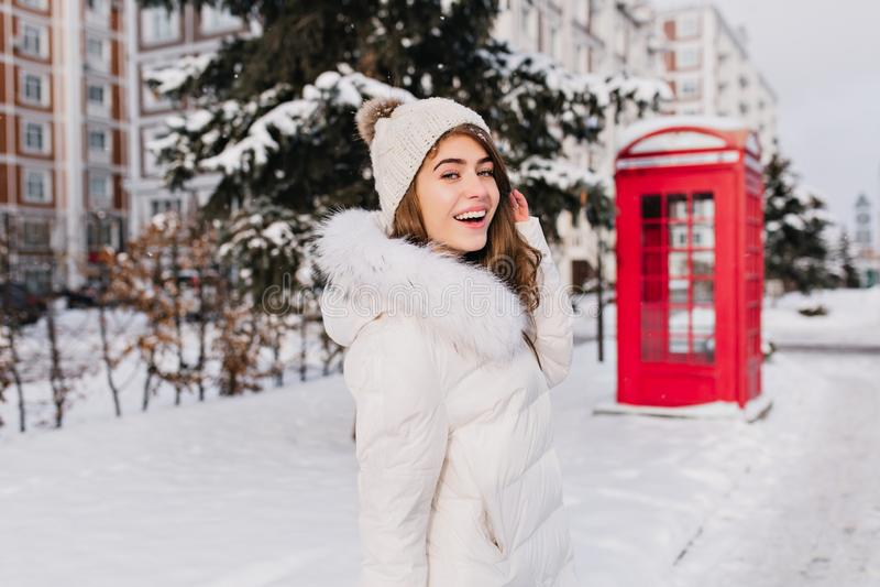 De blije Kaukasische vrouw in gebreide hoed gaat naar rode telefooncel in de winterdag Openluchtportret van aantrekkelijk Europee royalty-vrije stock fotografie