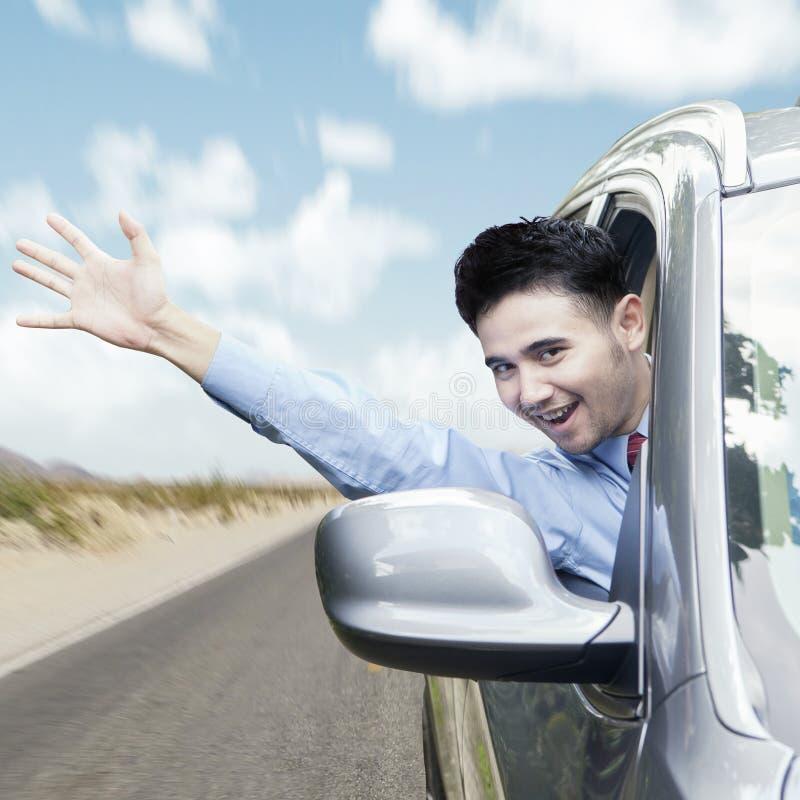 De blije mens die dient de auto in golven stock afbeelding