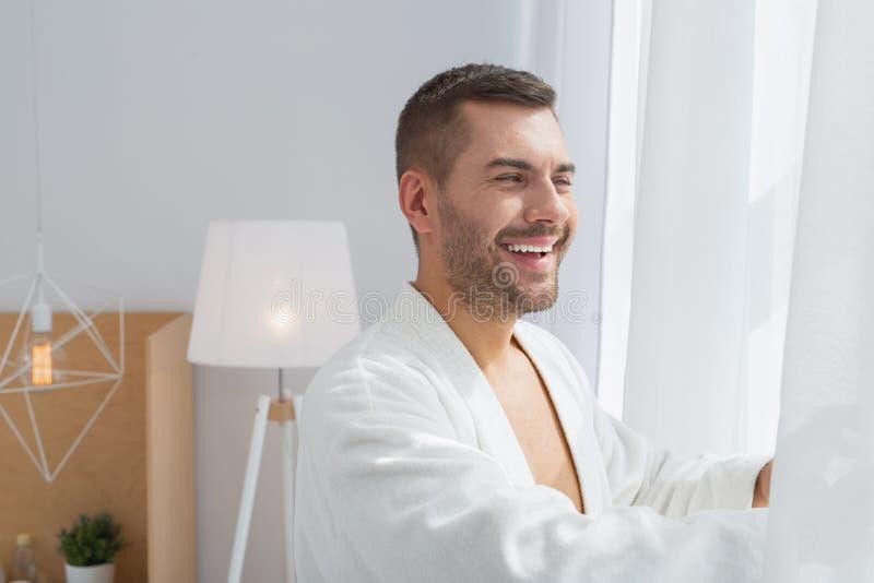 De blije mens die van Nice buiten het venster kijken stock foto