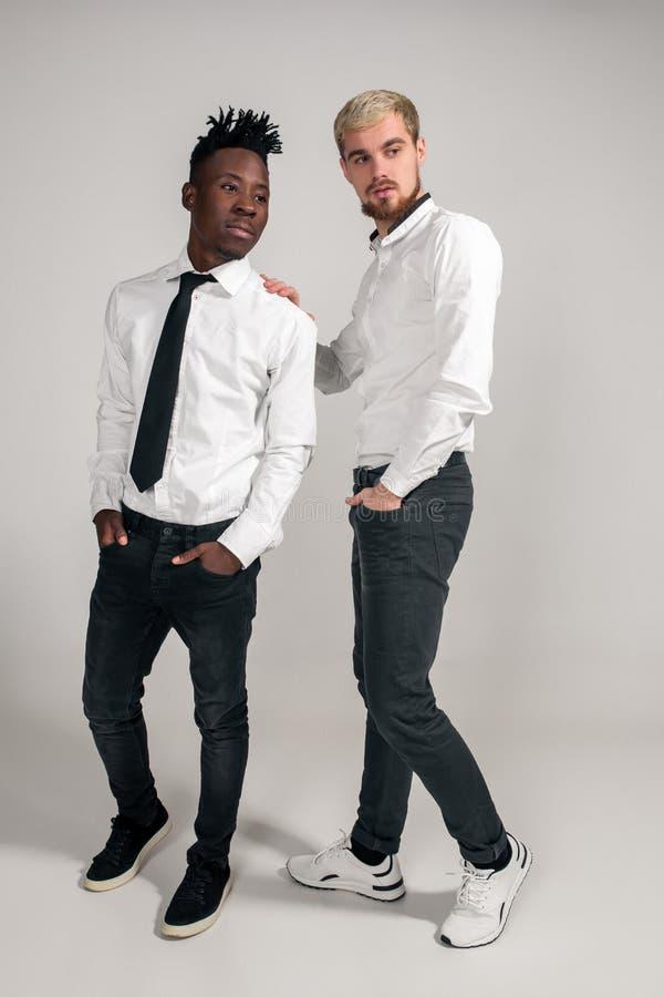 De blije ontspannen Afrikaanse en Kaukasische jongens in wit en zwart bureau kleedt het lachen en het stellen bij witte studio royalty-vrije stock afbeeldingen