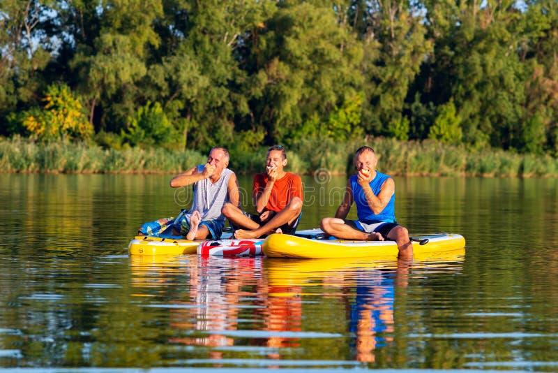 De blije vrienden, SUP surfers ontspannen, eten appelen en het hebben van pret royalty-vrije stock afbeeldingen