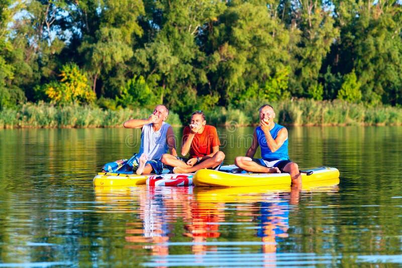 De blije vrienden, SUP surfers ontspannen, eten appelen en het hebben van pret royalty-vrije stock foto's