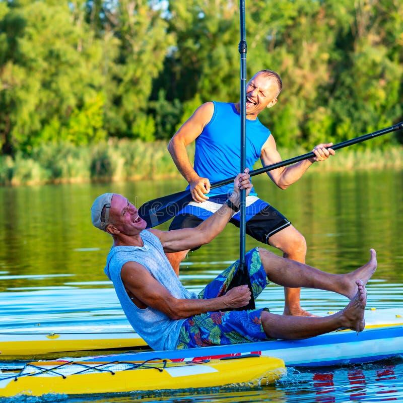 De blije vrienden, SUP surfers ontspannen op de grote rivier stock foto's
