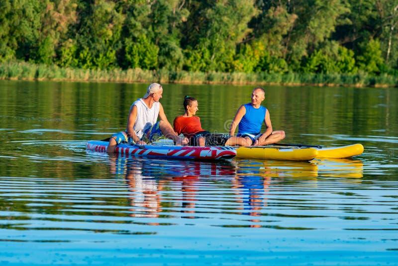 De blije vrienden, SUP surfers ontspannen op de grote rivier royalty-vrije stock afbeelding