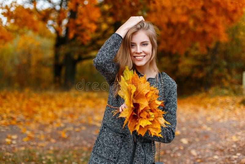 De blije vrij jonge gelukkige vrouw met een mooie glimlach in een elegante grijze laag met een boeket van de herfstbladeren stelt stock afbeeldingen