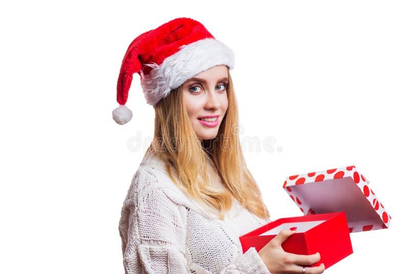 De blije vrolijke glimlachende blondevrouw in een rode Kerstmanhoed en een sweater opende haar nieuwe jaargift, een doos en bekij stock foto