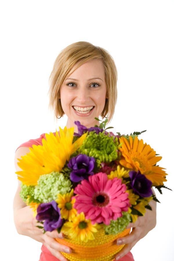 De blije vrouw biedt boeket aan stock fotografie