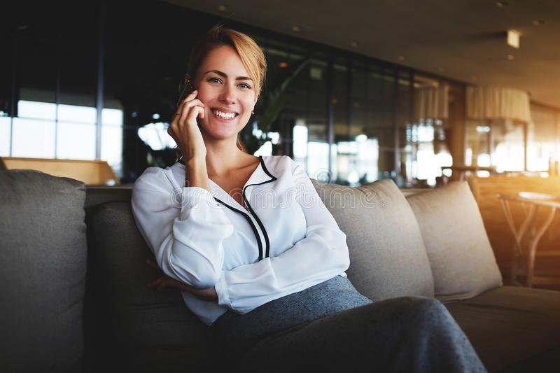 De blije vrouwelijke trog spreekt op celtelefoon met haar vriend tijdens rust in bar royalty-vrije stock afbeelding