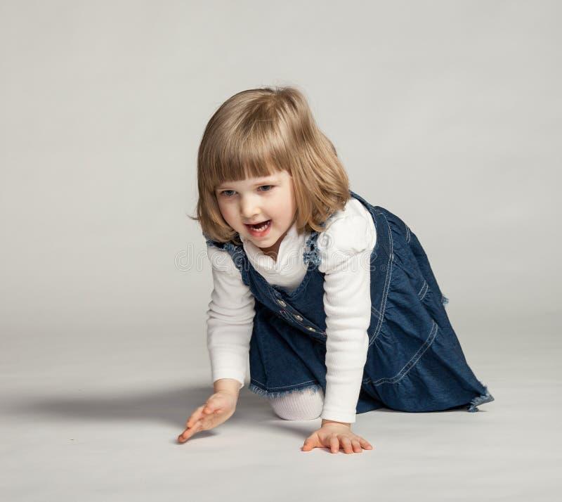 De blije zitting van het babymeisje op de vloer stock foto's