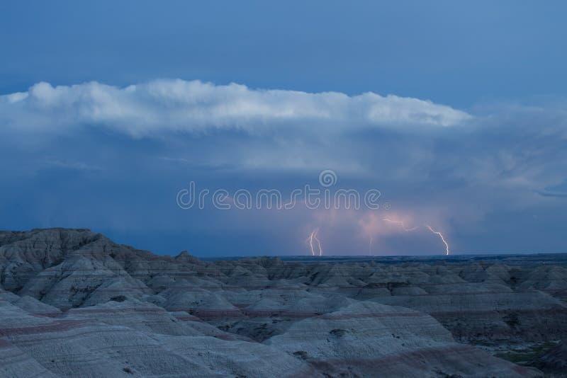 De bliksem slaat de horizon over een angstaanjagend landschap in het Nationale Park van Badlands royalty-vrije stock afbeelding