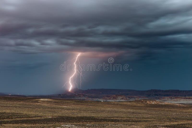 De bliksem slaat de klippen boven Meer Powell in Pagina, Arizona stock afbeelding