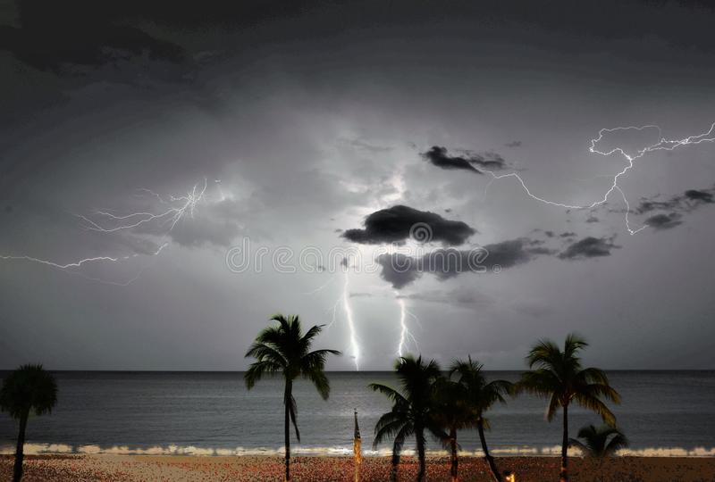 De bliksem wikkelt de de zomerhemel en de oceaan hieronder golven stock afbeelding