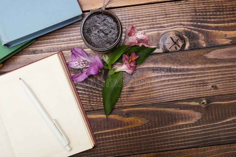 De blocnote, bloemen en schrobt op een houten lijst royalty-vrije stock afbeeldingen