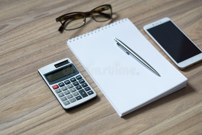 De blocnote, de calculator, smartphone, de glazen en de strook ballpen royalty-vrije stock foto