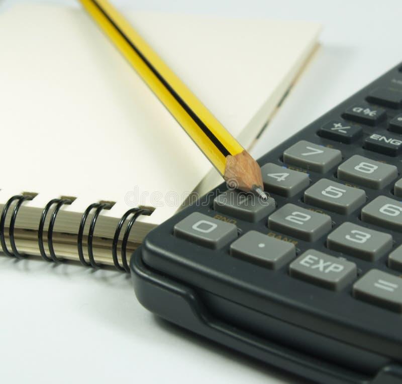 De blocnote en de calculator van het potlood stock afbeelding