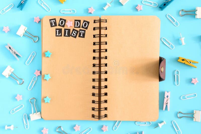 De blocnote op de lentes is open Naast de kantoorbehoeften Op de bruine pagina's van het notitieboekje is er een inschrijving royalty-vrije stock afbeelding