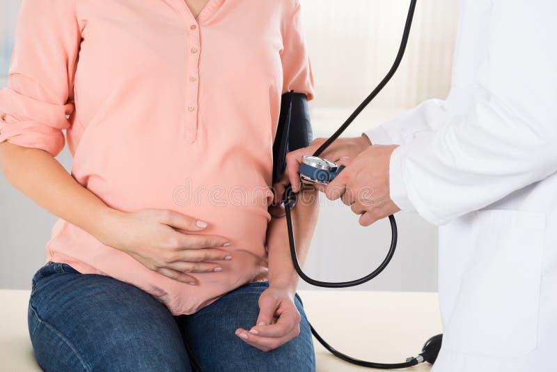 De Bloeddruk van artsenchecking pregnant woman stock foto