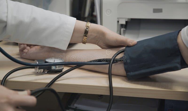 De bloeddruk van artsenmaatregelen van patiënt royalty-vrije stock afbeeldingen