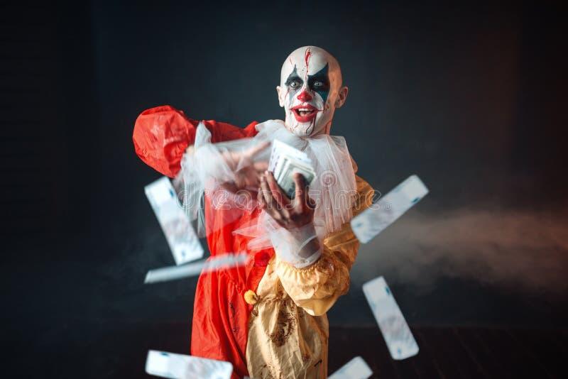 De bloedige clown met gekke ogen houdt ventilator van geld stock afbeeldingen