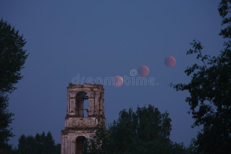 De bloedige maan over de Drievuldigheidskerk in Ukhta, Arkhangelsk-gebied stock foto
