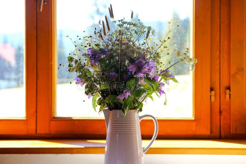 De bloem op tableA mooi boeket van wilde bloemen in een witte vaas bevindt zich op een vensterbank dichtbij het venster royalty-vrije stock foto's